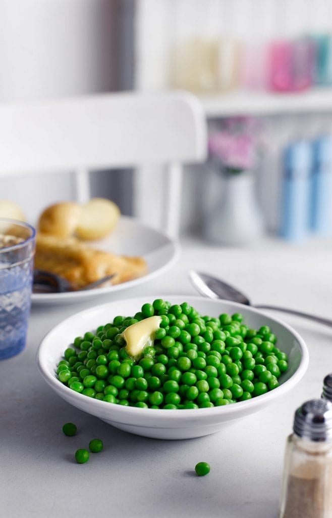 Cooked frozen peas with butter melted over the top