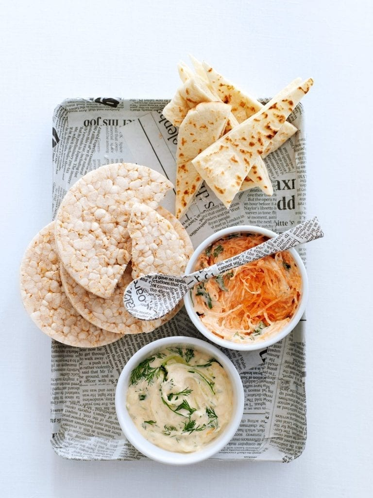 A tray of carrot and creamy dip served with pitta and rice cakes.