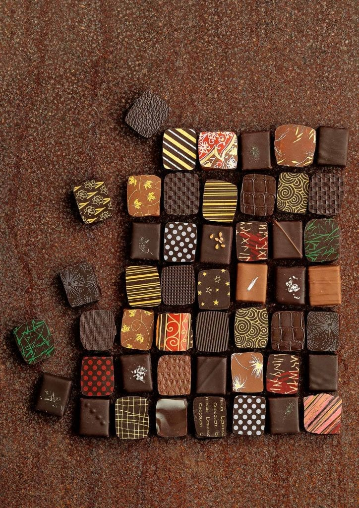 Small, decorated patterned chocolates arranged in a grid on a chocolate coloured surface similar to a mosaic.