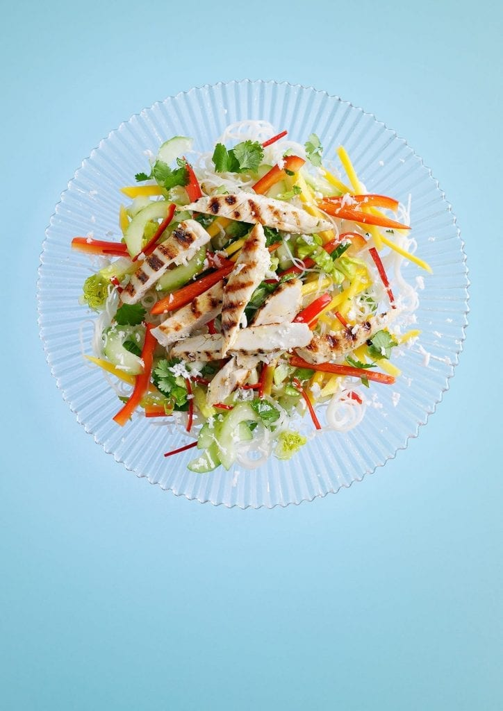 A crunchy mango and coconut salad on a clear plate and a blue background.