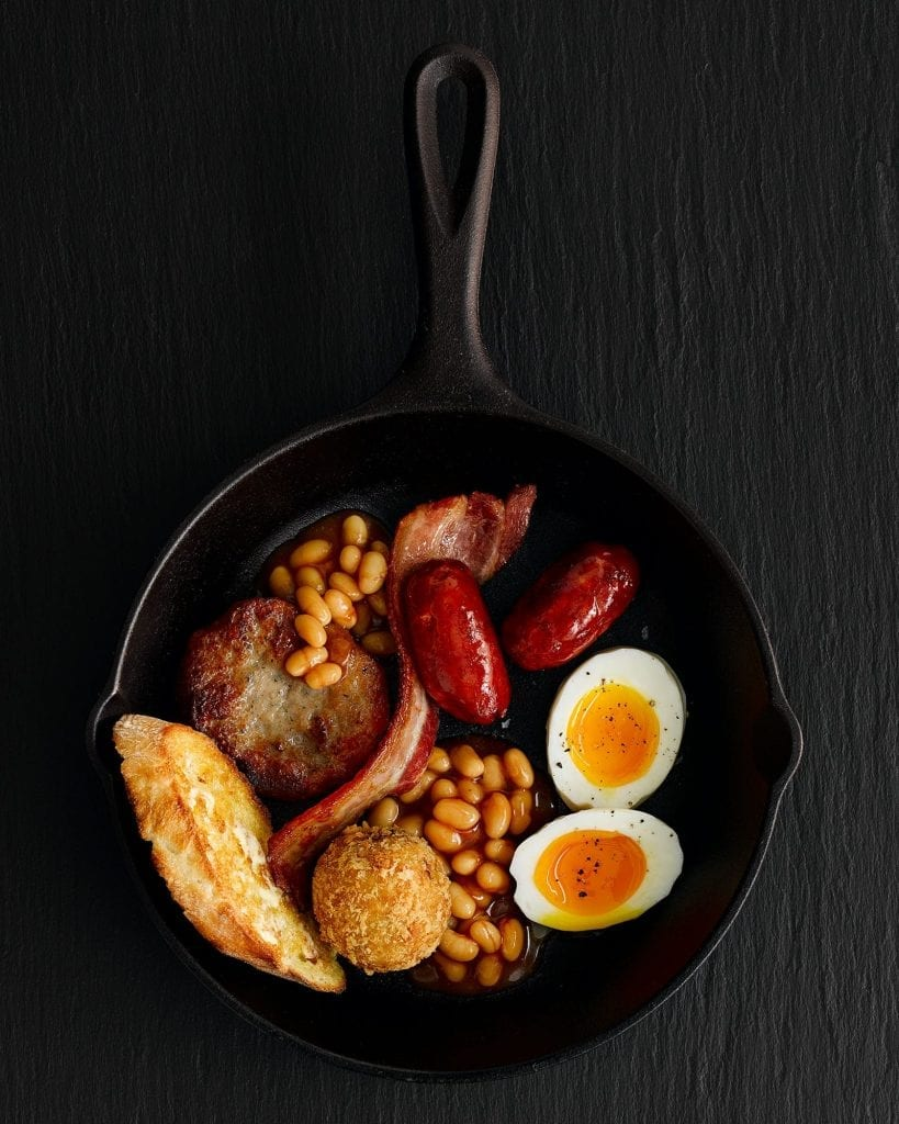 IBIS Fried breakfast of eggs, baked beans, fried bread, bacon, chorizo sausages and more served on a frying pan. Shot for IBIS.