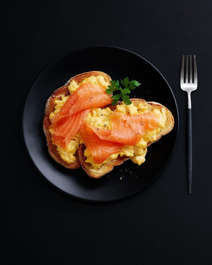 Shot for Marks and Spencer Hospitality Menus. Scrambled eggs and smoked salmon on toast. Graphic image shot on black plate with black background.