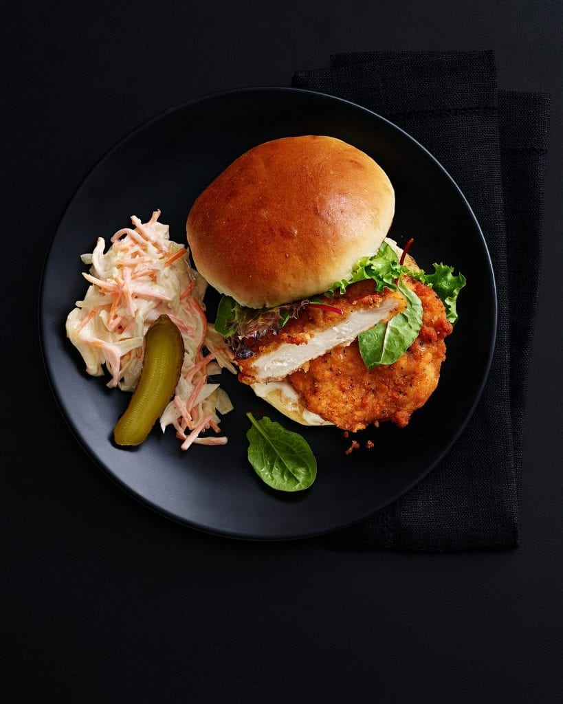 Shot for Marks And Spencer Hospitality Menus. Chicken burger with coleslaw and pickle. Graphic shot on black black with black background.