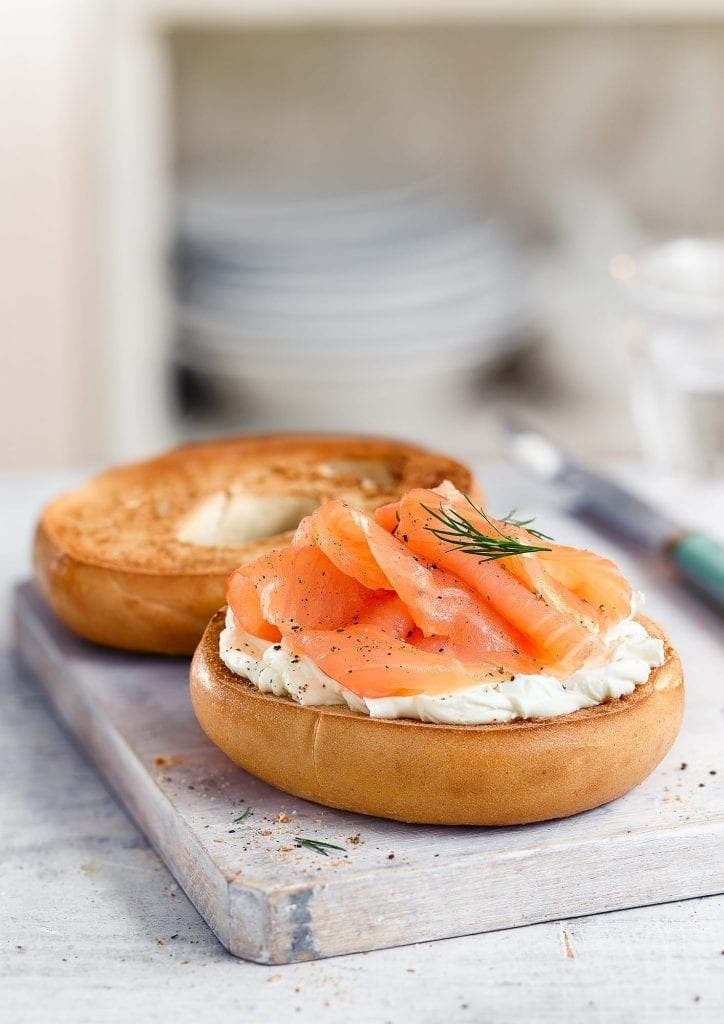 Salmon bagel with creme fraiche on chopping board