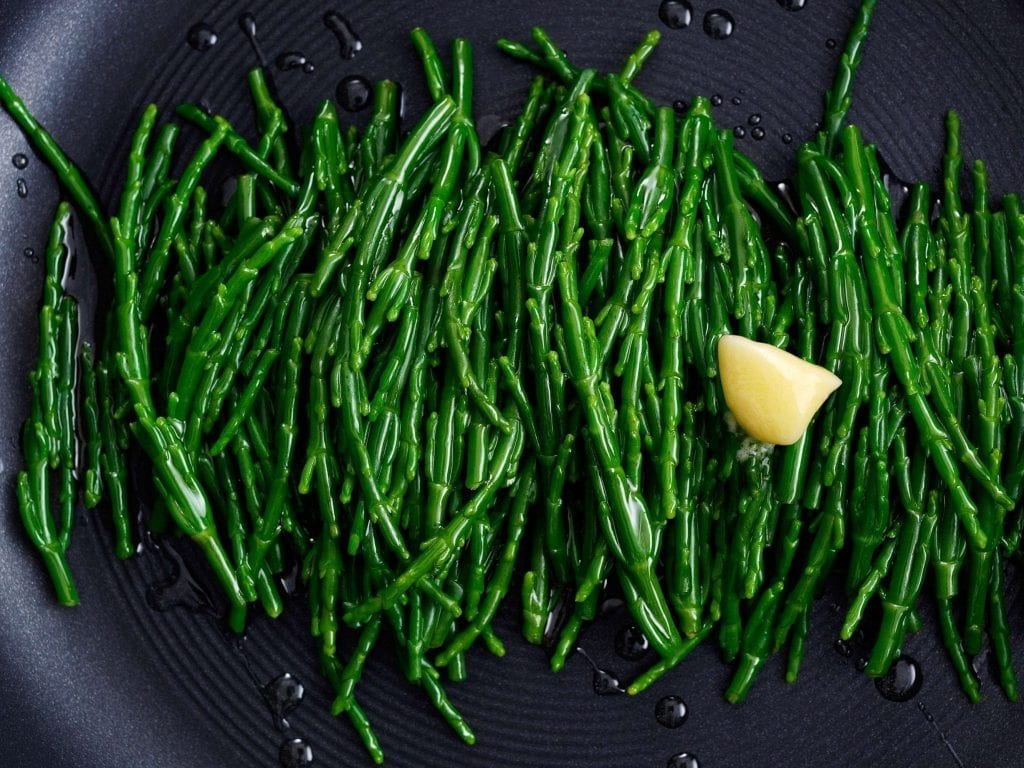 Personal shot of samphire being cooked with melting butter.