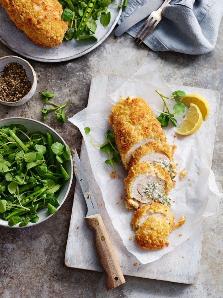 Chicken Kiev Watercress salad Sliced chicken breadcrumbs shot overhead with lemons